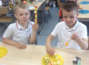 Putting the fruit on the skewer. Lochlan is ready to eat his.